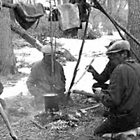 Indian trappers taking a noon break, boiling muskrat for lunch