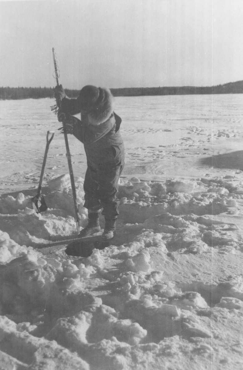 Commercial Fisherman Cutting Hole in Ice, Institute for Northern Studies fonds